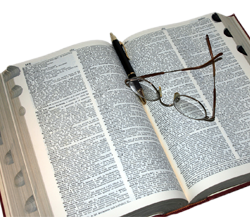 Eyeglasses resting on an open dictionary